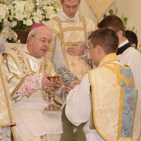 O ordenado toca o cálice, a patena e uma hóstia não consagrada.