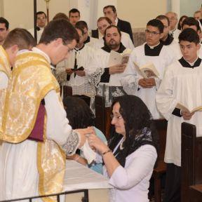 A mãe do ordenado desata a alfaia que amarra a mão consagrada de seu filho.
